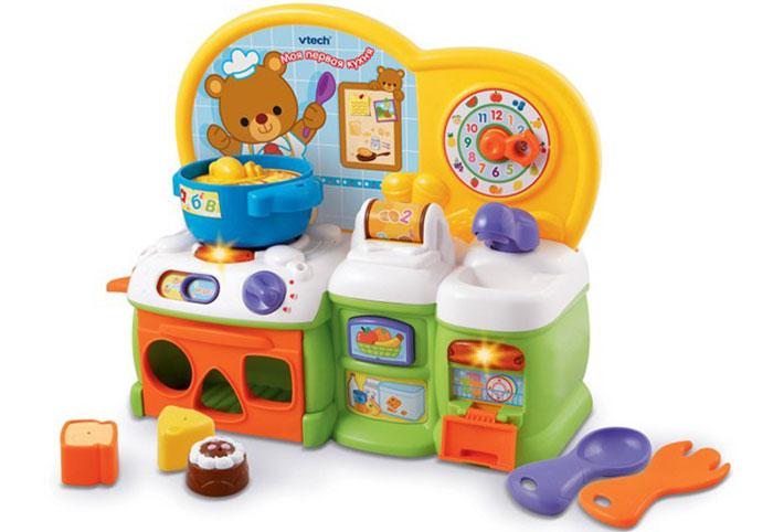 """Развивающая игрушка Vtech """"Моя первая кухня"""" непременно понравится маленькому поваренку, и поможет ему узнать много нового в веселой игровой форме. """"Моя первая кухня"""" - яркая кухня со звуковыми эффектами. Она состоит из варочной поверхности, съемной кастрюли, ложки и вилки. Также в комплект входят кусочек сыра, хлеб и шоколадный кекс. Игрушка выполнена из небьющегося пластика и подойдет для самых маленьких. Игрушка имеет 2 режима - """"Учеба"""" и """"Игра"""", которые переключаются простым движением рычажка. В режиме """"Учеба"""" малыш сможет приготовить алфавитный суп, раскатать тесто для печенья и помыть посуду, когда все будет готово. Сначала игрушка предложит малышу приготовить суп - для этого нужно вращать диск в кастрюльке, при этом будет играть веселая мелодия и забавное бульканье. Малыш сможет вращать ролик с изображением печенья и цифр от 1 до 4, а игрушка споет веселую песенку. При нажатии на кран раздастся реалистичный звук льющейся воды, а игрушка расскажет..."""