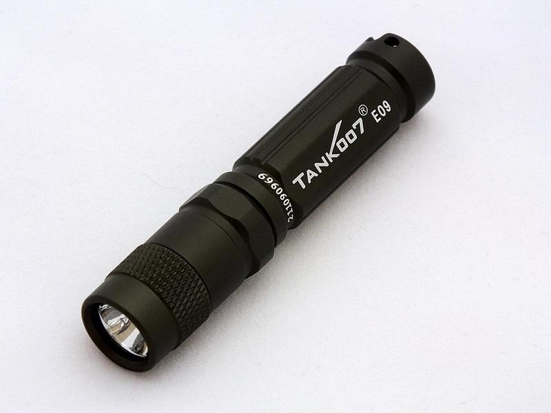 Фонарь светодиодный TANK007 E09, с комплектацией, цвет: графитE09GВысококачественный карманный светодиодный фонарь-брелок TANK007 E09 - самый компактный в своем классе. Фонарь выполнен из авиационного алюминия с III (наивысшей) степенью защитного анодирования корпуса. Водонепроницаемый — стандарт IPX8. Фонарь снабжен современным светодиодом CREE XP-E R3 (США) и встроенным стабилизатором напряжения. Особенности конструкции: - три режима работы фонаря: High (полная мощность), Medium (средний режим), Low (экономичный режим); - имеется функция памяти - при последующем включении фонарь начинает работать в выбранном ранее режиме; - включение и переключение режимов работы осуществляется вращением головной части фонаря - кратковременное вращение на четверть оборота вправо - влево до фиксации; - фонарь работает от одной батарейки ААА (в комплекте); - резиновое уплотнение в хвостовике фонаря; - при использовании светорассеивающего наконечника фонарь работает в режиме кемпинговой лампы. Комплектация:- фонарь в алюминиевой коробке - батарейка ААА- кольцо для брелока - комплект запасных резиновых уплотнителей.Мощность светового потока: до 120 люмен.Дальность эффективного излучения света: до 80 метров.