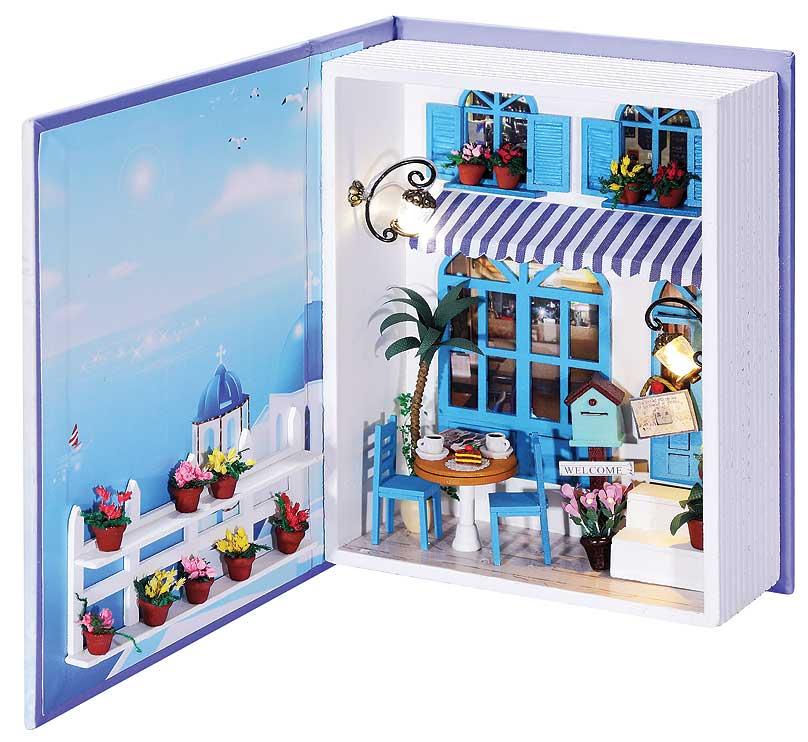 """Набор для создания румбокса (миниатюры) """"Кафе в Санторини"""".   Коллекционные наборы для создания миниатюр или как их еще называют румбокс, представляют из себя коробку-витрину для демонстрации трехмерных моделей, которые выполнены в определенном масштабе. Миниатюрой может быть часть улицы, комната, кафе, домик или просто красивый уголок природы. Из набора для создания миниатюры вам предстоит построить небольшую модель кафе с мебелью и деталями интерьера. Самостоятельно из деталей постройте стены кафе, сделайте мебель, цветы и даже проведите освещение. Все детали расфасованы по пакетам и с помощью инструкции на русском языке вы поэтапно построите миниатюру.    Основа миниатюры """"Кафе в Санторини"""" - коробочка в форме толстой книги, вы можете держать ее открытой, а если закроете, то можно легко переносить или хранить на полке.       В набор входят:  - основа миниатюры: книжка - коробочка, - детали интерьера в разборе, - клей, - ножницы, - пинцет, - диодное освещение, - пошаговая инструкция на русском языке с иллюстрациями."""