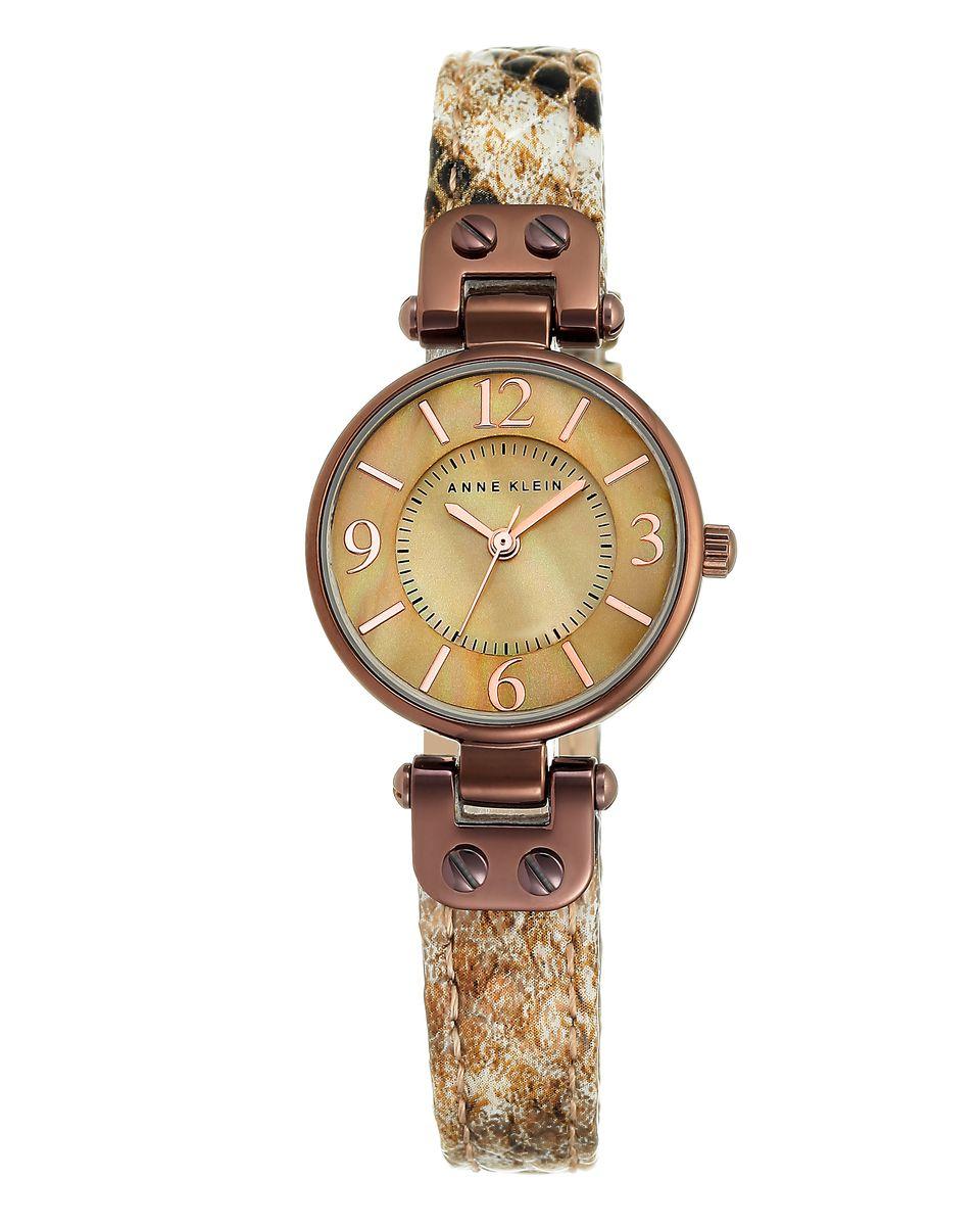 Часы наручные женские Anne Klein Ring, цвет: бежевый. 9443BM8434-58AEЭлегантные женские часы Anne Klein Ring выполнены из металлического сплава, оформлены символикой бренда. Циферблат украшен вставкой из натурального перламутра. Лаконичный корпус надежно защищен устойчивым к царапинам минеральным стеклом, а также имеет степень влагозащиты 3 Bar. Часы оснащены кварцевым механизмом, дополнены изящным ремешком из натуральной кожи с декоративным тиснением под кожу рептилии. Ремешок застегивается на практичную пряжку.Часы поставляются в фирменной упаковке.Часы Anne Klein Ring подчеркнут изящество женской руки и отменное чувство стиля у их обладательницы.