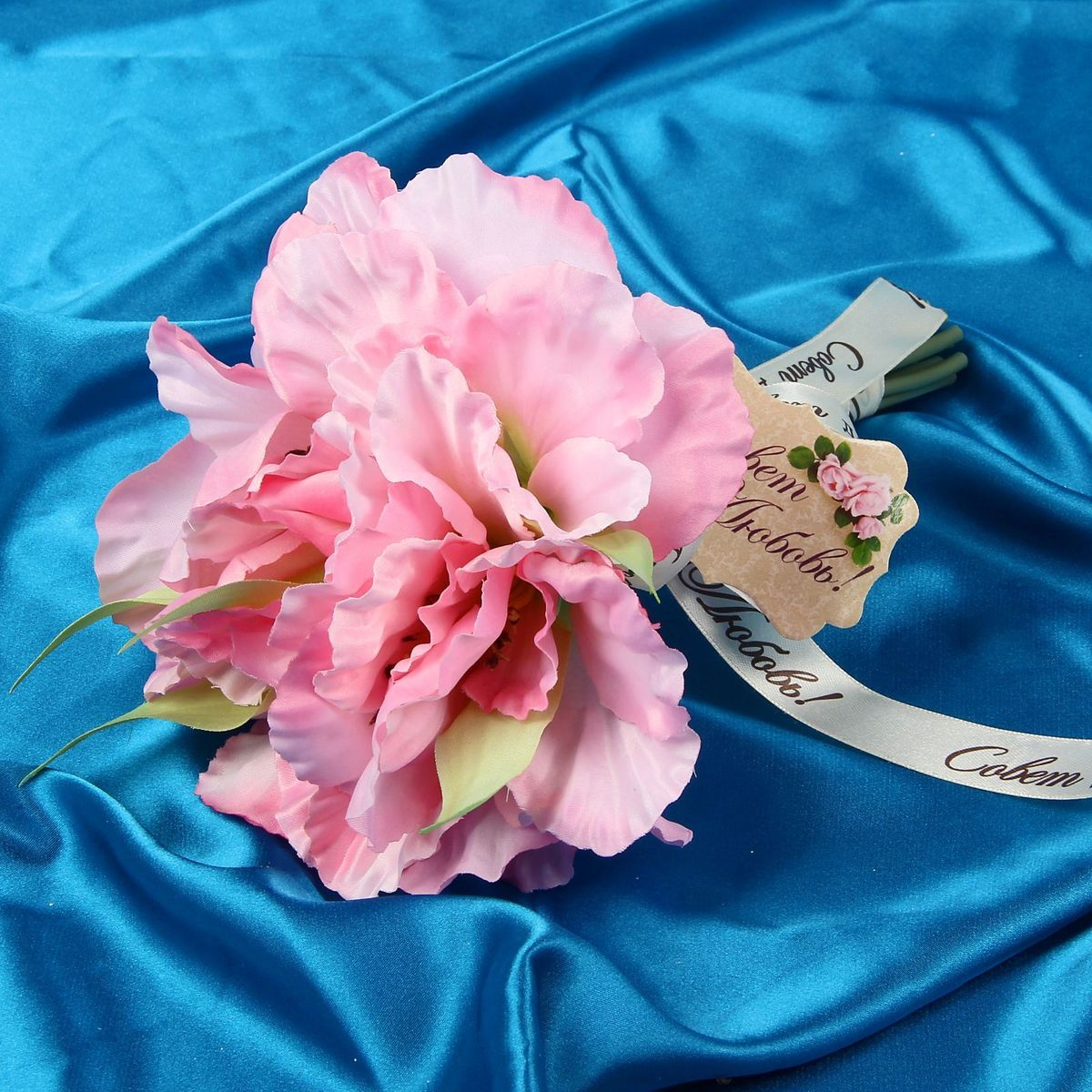 Букет-дублер Sima-land Лилос, цвет: розовый09840-20.000.00Свадьба - одно из главных событий в жизни человека. В такой день всё должно быть безупречно, особенно букет невесты. Но кидать, по старой традиции, цветочную композицию подругам не всегда удобно, и на помощь приходит букет-дублер Лилос - красивый и яркий аксессуар. Стебли оформлены лентой с надписью Совет да любовь. Букет дополнен шильдом с тёплым пожеланием. После торжества он украсит любой интерьер, ведь нежные цветы из текстиля не завянут и не помнутся.