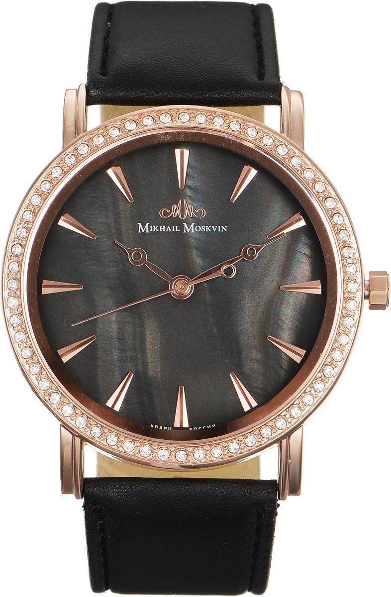 Часы наручные женские Mikhail Moskvin Каприз, цвет: черный, золотой. 586-8-4EQW-M710DB-1A1Стильные женские наручные часы Mikhail Moskvin Каприз изготовлены из высокотехнологичной гипоаллергенной нержавеющей стали и дополнены ремешком из искусственной кожи, охватываемый двойными элегантными ушами. Для того чтобы защитить циферблат от повреждений в часах используется высокопрочное минеральное стекло.Модель выпускается с высокоточным японским кварцевым механизмом, производства фирмы Seiko Epson, который оснащен часовой, минутной и секундной стрелками.Корпус традиционной формы, рант которого украшают сверкающие стразы. Часы и минуты отображаются с помощью объемных золотистых знаков и стрелок в стиле Бреге на поле циферблата из темного перламутра.Браслет комплектуется надежной и удобной в использовании застежкой-пряжкой, которая позволит с легкостью снимать и надевать часы, а также регулировать длину браслета.Часы упакованы в блистер.Часы Mikhail Moskvin для современных и стильных людей, которые стремятся выделиться из толпы и подчеркнуть свою индивидуальность.