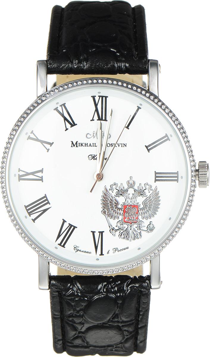 Часы наручные мужские Mikhail Moskvin, цвет: черный, серебристый. 1128A1L1BM8434-58AEСтильные мужские наручные часы Mikhail Moskvin изготовлены из высокотехнологичной гипоаллергенной нержавеющей стали и дополнены ремешком из искусственной кожи. Для того чтобы защитить циферблат от повреждений в часах используется высокопрочное минеральное стекло. Тонкие скругленные уши, фиксирующие черный ремень, стилизованный под кожу крокодила, дополнены с боков винтами. Черные римские цифры на белом поле циферблата и скошенная к центру рамка с круглыми часовыми индексами придают часам стильность. Серебристый герб - символ России - отлично гармонирует с тонкими стальными стрелками. Высокоточный японский кварцевый механизм, производства фирмы Seiko Epson, отвечает за работу часовой, минутной и секундной стрелок и обладает степенью влагозащиты равной 3 Bar. Эта великолепная модель часов сочетает в себе элегантность и надежность.Браслет комплектуется надежной и удобной в использовании застежкой-пряжкой, которая позволит с легкостью снимать и надевать часы, а также регулировать длину браслета.Часы упакованы в блистер.Часы Mikhail Moskvin подчеркнут мужской характер и отменное чувство стиля их обладателя.