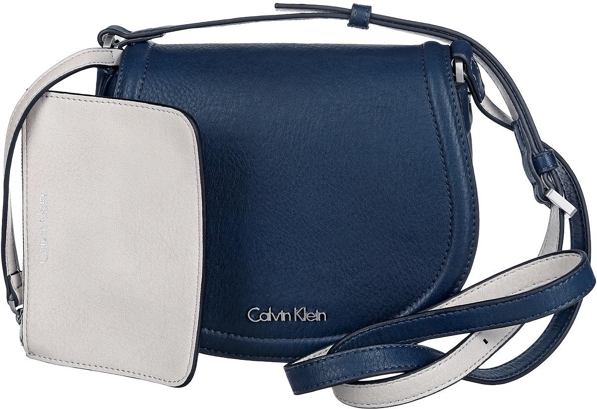 Сумка женская Calvin Klein Jeans, цвет: темно-синий. K60K601646_902010130-11Стильная сумка Calvin Klein выполнена из искусственной кожи с зернистой фактурой, оформлена металлической фурнитурой с логотипом бренда.Изделие содержит одно отделение, которое закрывается клапаном на магнитную кнопку. Внутри сумки размещены накладной кармашек для мелочей и врезной карман на застежке-молнии. Сумка оснащена практичным плечевым ремнем регулируемой длины. В комплекте с изделием поставляется небольшой кошелек на застежке-молнии, который фиксируется к сумке при помощи карабина, и чехол для хранения.Модная сумка идеально подчеркнет ваш неповторимый стиль.