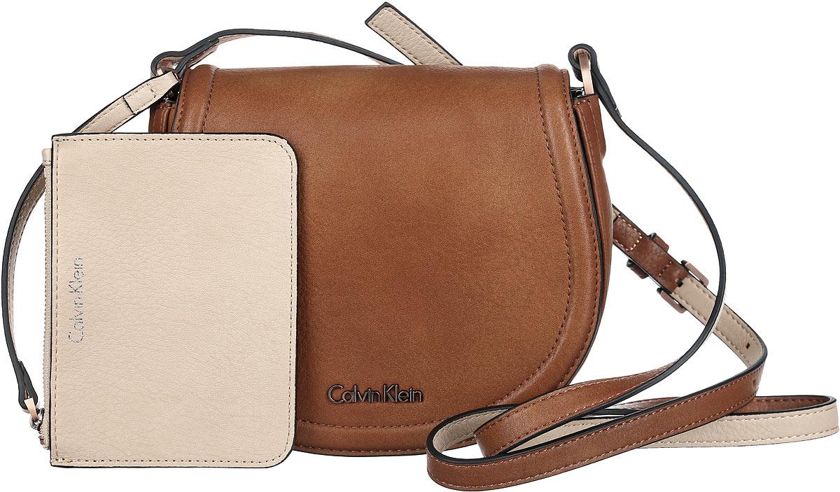 Сумка женская Calvin Klein Jeans, цвет: коричневый. K60K601646_9010K60K601646_9010Стильная сумка Calvin Klein выполнена из искусственной кожи с зернистой фактурой, оформлена металлической фурнитурой с логотипом бренда.Изделие содержит одно отделение, которое закрывается клапаном на магнитную кнопку. Внутри сумки размещены накладной кармашек для мелочей и врезной карман на застежке-молнии. Сумка оснащена практичным плечевым ремнем регулируемой длины. В комплекте с изделием поставляются небольшой кошелек на застежке-молнии, который фиксируется к сумке при помощи карабина, и чехол для хранения.Модная сумка идеально подчеркнет ваш неповторимый стиль.