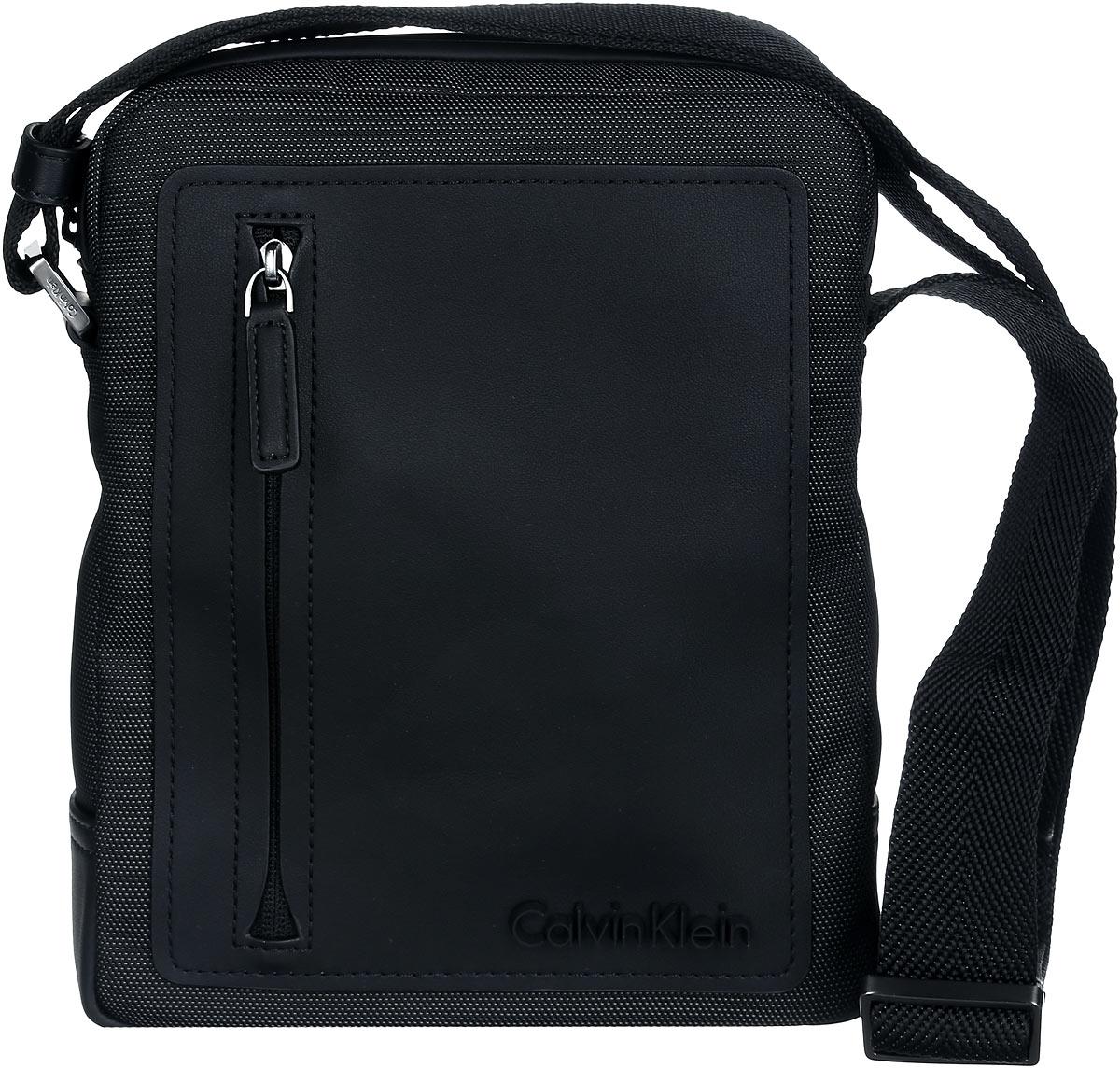 Сумка мужская Calvin Klein Jeans, цвет: черный. K50K501618_0010K50K501618_0010Стильная сумка Calvin Klein выполнена из полиуретана, оформлена символикой бренда.Изделие содержит одно отделение, которое закрывается на застежку-молнию. Внутри сумки размещены два накладных кармашка для мелочей и врезной карман на застежке-молнии. Сумка оснащена плечевым ремнем регулируемой длины. Лицевая сторона дополнена накладным карманом на молнии. В комплекте с изделием поставляется чехол для хранения.Модная сумка идеально подчеркнет ваш неповторимый стиль.