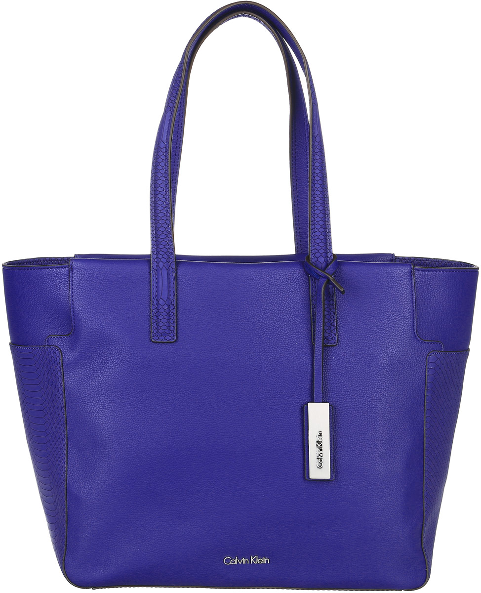Сумка женская Calvin Klein Jeans, цвет: синий. K60K602240_4330A16-11162_138Стильная сумка Calvin Klein не оставит вас равнодушной благодаря своему дизайну и практичности. Она изготовлена из качественного полиуретана и оформлена тиснением под рептилию. Лицевая сторона оформлена металлической пластинкой с названием бренда. Сумка оснащена удобными ручками, которые дополнены ремешком с фирменной металлической пластинкой. Изделие закрывается на удобную молнию. Внутри расположено одно вместительное отделение, которое содержит три открытых накладных кармана для телефона и мелочей и один вшитый карман на молнии. Такая модная сумка подчеркнет ваш неповторимый образ и займет достойное место в вашем гардеробе.