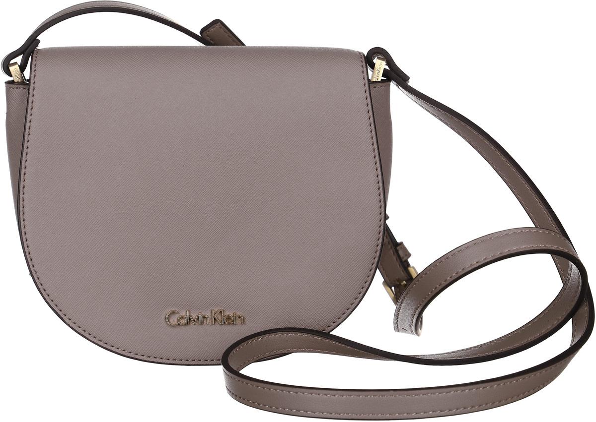 Сумка женская Calvin Klein Jeans, цвет: капучино. K60K602148_0940KV996OPY/MМиниатюрная сумка Calvin Klein не оставит вас равнодушной благодаря своему дизайну. Она изготовлена из ПВХ и оформлена металлической пластинкой с названием бренда. Сумка оснащена удобным плечевым ремнем, длина которого регулируется с помощью пряжки. Изделие закрывается клапаном на магниты. Внутри расположено отделение, которое содержит один открытый накладной карман.Такая стильная сумка подчеркнет ваш неповторимый образи займет достойное место в вашем гардеробе.
