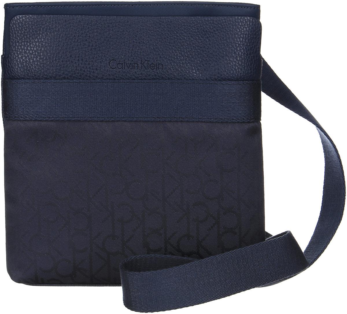 Сумка мужская Calvin Klein Jeans, цвет: темно-синий. K50K502124_0000A16-42010_205Стильная сумка Calvin Klein не оставит вас равнодушным благодаря своему дизайну и практичности. Она изготовлена из качественной искусственной кожи зернистой текстуры с элементами из полиэстера и оформлена фирменной тисненой надписью и принтом. На лицевой части расположен накладной карман, который закрывается на магнит. Изделие закрывается на удобную молнию. Внутри расположено главное отделение, которое содержит два открытых накладных кармана для телефона и мелочей и один вшитый карман на молнии. Такая удобная и модная сумка станет незаменимой вещью в вашем гардеробе.