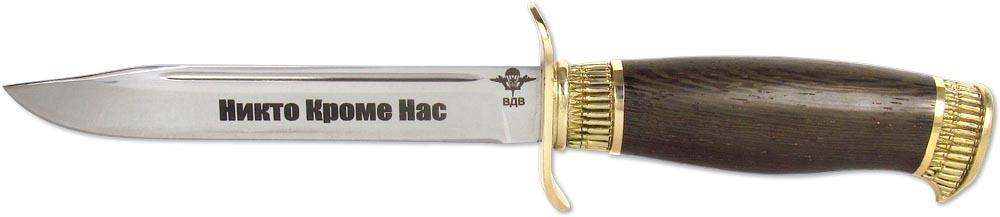 Нож Ножемир Разведчик. Никто кроме нас, кованая сталь, с ножнами, общая длина 27 см. (1836)к743840Легендарный нож Ножемир Разведчик. Никто Кроме Нас обладает клинком со скосом обуха (щучка, клип-пойнт), S-образным перекрестием гарды, спуски занимают около половины ширины клинка. Нож, выполненный из кованой стали, отличается качественным и эстетически гармоничным исполнением. Клинок ножа имеет зеркальную полировку и лазерную гравировку эмблемы ВДВ и надписи Никто Кроме Нас. Рукоять ножа выполнена из дерева венге и обрамлена художественным латунным литьем, изображающим патронную ленту. Нож комплектуется аккуратными красивыми ножнами из натуральной кожи коричневого цвета с прострочкой.Общая длина ножа: 27 см.