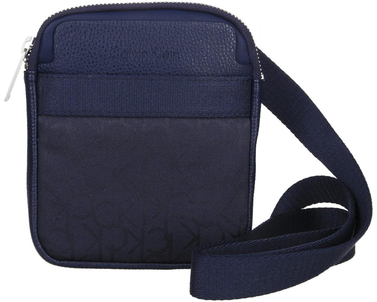Сумка мужская Calvin Klein Jeans, цвет: темно-синий. K50K502138_000101225Стильная сумка Calvin Klein Jeans выполнена из поливинилхлорида с добавлением хлопка и полиэстера, оформлена символикой бренда. Изделие содержит одно отделение, которое закрывается на застежку-молнию. Внутри сумки размещен один накладной кармашек для мелочей и один прорезной на застежке-молнии. Спереди расположен один открытый накладной карман. Сумка оснащена плечевым ремнем регулируемой длины. В комплекте с изделием поставляется чехол для хранения.