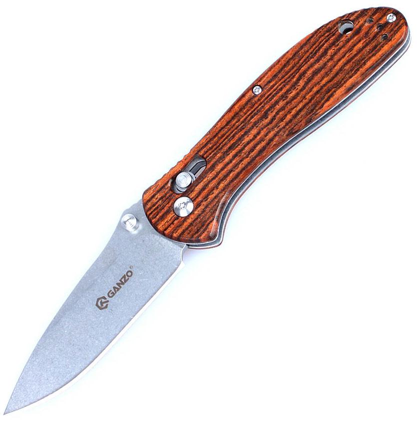 Нож туристический Ganzo, цвет: коричневый, темно-коричневый, стальной, длина лезвия 8,7 см. G7392-WD1G7392-WD1Нож Ganzo сделан удобным и практичным для использования в любой поездке. Он подойдет для туризма, пикников, выездов на рыбалку или же полевого использования в повседневной жизни. Нож не ржавеет, компактно складывается и легко затачивается.Этот нож получил привлекательный современный дизайн на основе классического облика карманного ножа. Он сделан из долговечных материалов, которые станут залогом длительной и практичной службы ножа. Для клинка решено было использовать нержавеющую сталь, за которой нужен минимальный по затратам времени и усилий уход. Таким требованиям соответствует марка 440С с высокой степенью защищенности от ржавления и достаточной твердостью, чтобы нож оставался острым в течении всей поездки. По длине лезвие равно 8,7 см. Производители придали ему форму drop-point и гладко заточили по всей длине. Еще одна особенность — это матовая поверхность металла. Она получается путем шлифовки клинка перекатывающимися камнями. В итоге, нож становится тактическим, поскольку не бликует, и более практичным для туристов. На нем не остаются отпечатки пальцев, не видны случайные царапины и неаккуратности заточки.Для рукоятки сделаны две деревянные накладки. Этот материал выбран за экологичность и хорошие эксплуатационные данные. Древесина плотная, тщательно отшлифованная и обработана, чтобы не впитывать воду. Она окрашена таким образом, что светло-коричневые полосы чередуются с темными.В рукоятку встроен штифтовой замок для ножей под названием Axis. Он фиксирует клинок открытым, упираясь в его пятку, делая работу с ним полностью безопасной. Теперь нож не сложится даже под рабочей нагрузкой. А в качестве страховки от потери ножа во время его переноски, можно использовать стальную клипсу или вдеть в отверстие на рукоятке шнурок, чтобы закрепить нож на лямке рюкзака.Общая длина ножа: 20,5 см.Длина лезвия: 8,7 см.Вес ножа: 122 г.