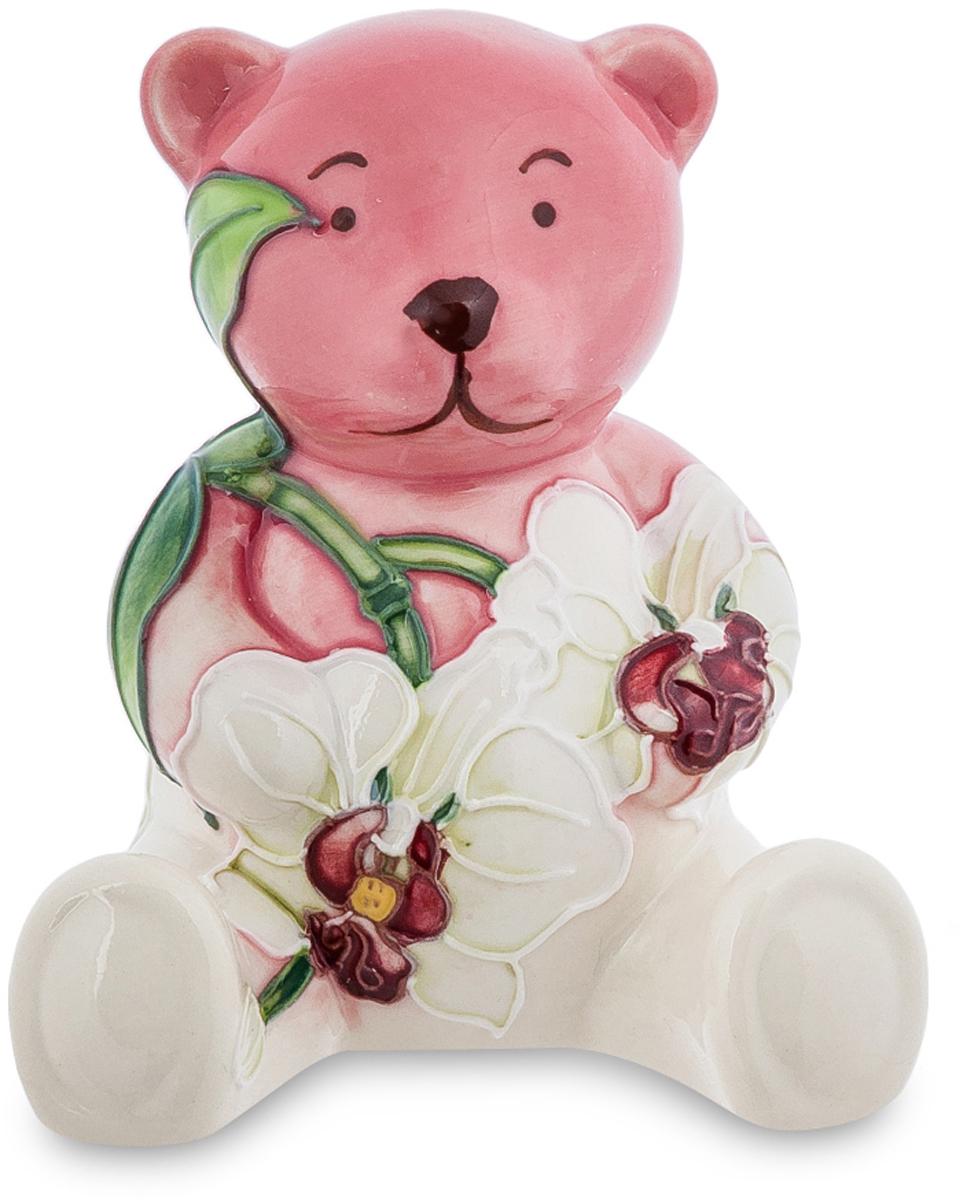 Фигурка Pavone Медвежонок. JP-98/5274-0120Фигурка Медвежонок (Pavone)Игрушечного медвежонка забыли в траве и растения начали его заплетать, пропустив побеги вдоль спинки, прикрыв лапы белыми цветами с красными сердцевинками. А медвежонок терпит, хоть ему и щекотно, и внимательно смотрит перед собой нарисованными точечками-глазками: ну где же там моя маленькая хозяйка, я ведь, хоть и красивым стал среди этих цветов, но все равно скучаю в одиночестве. Такой сувенир может послужить интересным украшением комнаты, особенно той, где живет маленькая девочка. Пусть она привыкает не забывать никогда своих игрушек на прогулке. Они же будут скучать!
