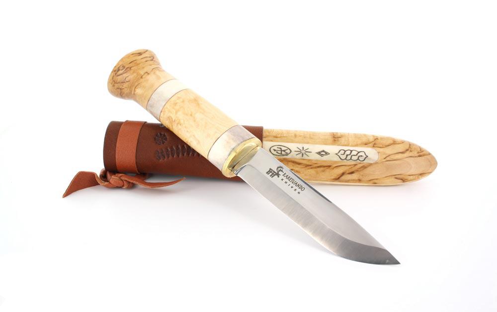 """Нож Karesuando Wolverine, цвет: светло-коричневый, длина клинка 9,9 см. KR/3513KR/3513Изготовленный из высококачественной стали Sandvik12C27 клинок, обеспечивает качественный рез, хорошо держит режущую кромку и легко поддается заточке. Вы не ощутите ни малейшего дискомфорта при работе с ним. Рукоять ножа выполнена из карельской березы и инкрустирована вставками из рога оленя, что придает ножу особый колорит и выделяет на фоне многих других оппонентов в ножевой среде. Ножны """"Росомахи"""" выполнены из натуральной кожи, массива карельской березы и украшены вставкой из рога оленя с этническим узором, придавая ножу неповторимый Лапландский дух.Общая длина ножа: 21 см.Длина клинка: 9,9 см.Толщина клинка: 3,3 мм.Длина рукояти: 11,1 см.Толщина рукояти: 2,1 см."""