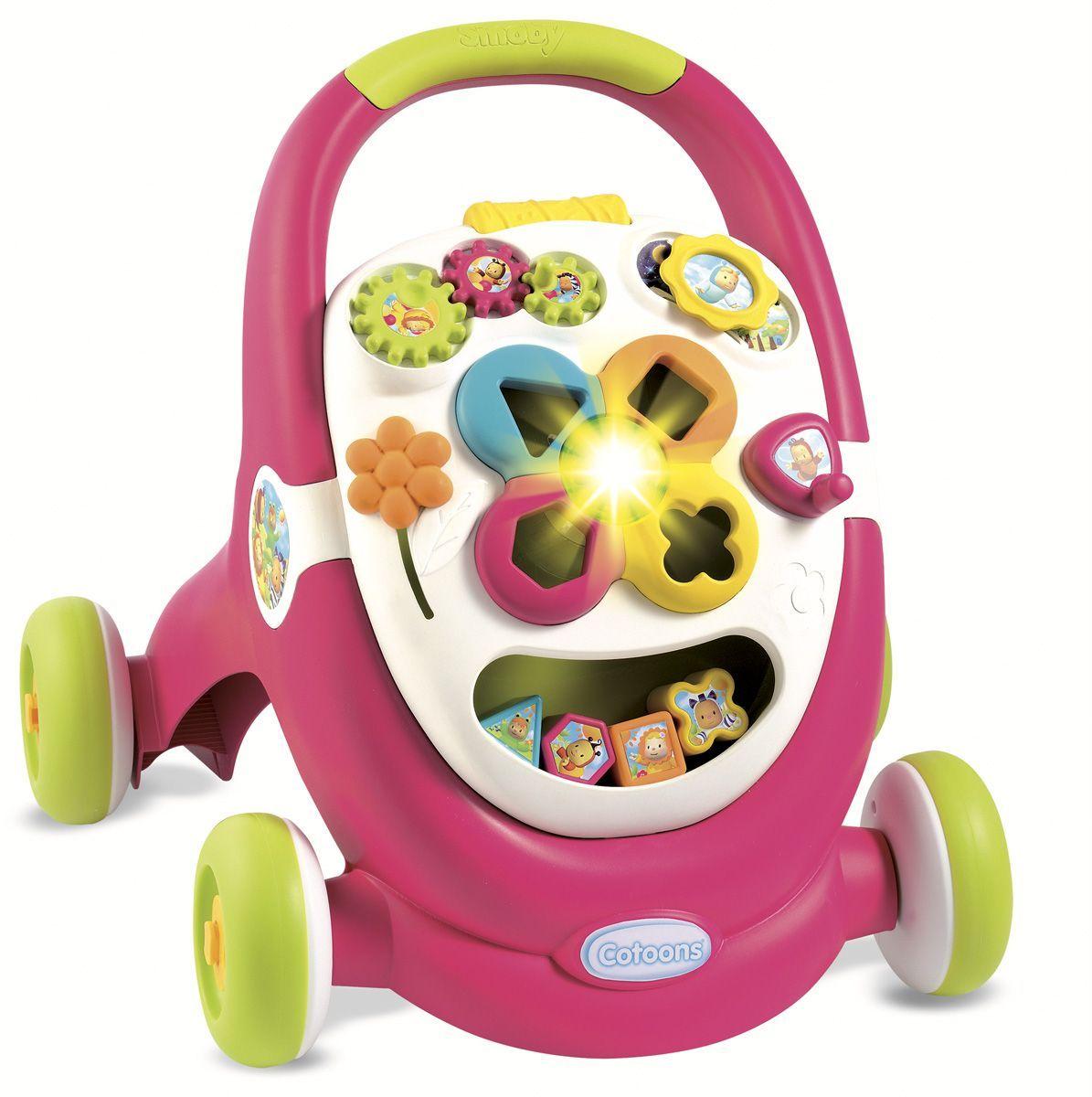 """Ходунки-каталка Smoby """"Cotoons"""" помогают малышам делать первые шаги безопасно. Колеса каталки блокируются, чтобы ребенок мог спокойно стоять или играться. Игровая панель оснащена световыми и звуковыми эффектами. Ходунки снабжены сортером, который помогает в изучении форм и цвета. Также на панели есть игровые шестеренки, цветочек и рычаг."""