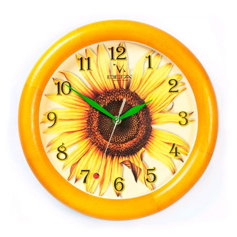 Часы настенные Вега Подсолнух. Д1К/7-15Д1К/7-15Оригинальные настенные часы круглой формы Вега Подсолнух выполнены из дерева и пластика. Часы имеют три стрелки - часовую, минутную и секундную. Необычное дизайнерское решение и качество исполнения придутся по вкусу каждому. Оформите свой дом таким интерьерным аксессуаром или преподнесите его в качестве презента друзьям, и они оценят ваш оригинальный вкус и неординарность подарка.Часы работают от 1 батарейки типа АА напряжением 1,5 В (в комплект не входит).