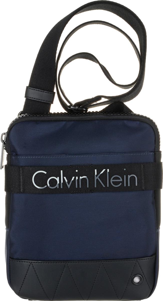 Сумка мужская Calvin Klein Jeans, цвет: темно-синий. K50K502291_4380H002Стильная сумка Calvin Klein Jeans выполнена из полиуретана с добавлением полиамида и полиэстера. Изделие содержит одно большое отделение, которое закрывается на застежку-молнию. Внутри сумки размещен один кармашек на застежке-молнии. Спереди сумка также дополнена накладным карманом на застежке-липучке. Модель оснащена плечевым ремнем регулируемой длины.