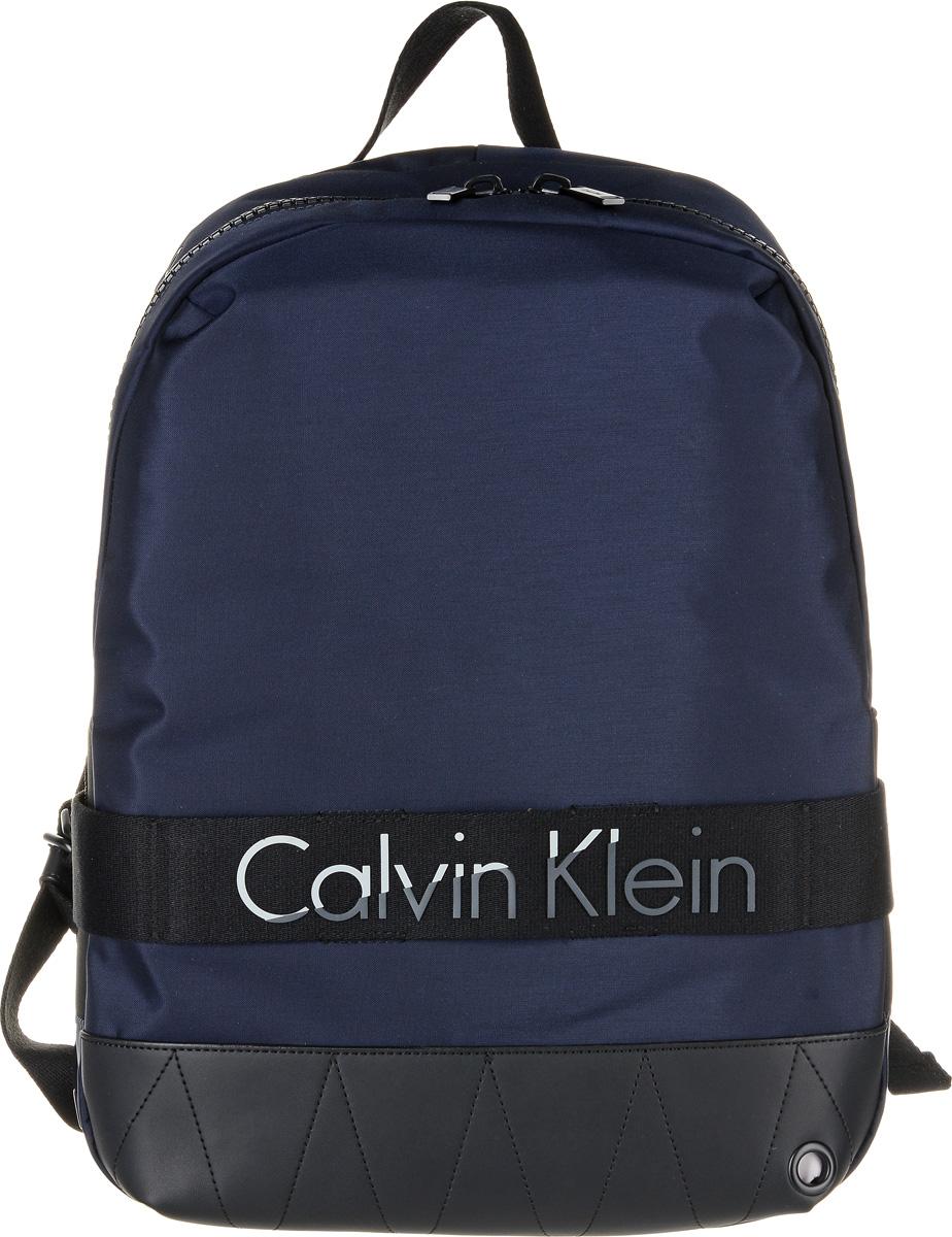 Рюкзак мужской Calvin Klein Jeans, цвет: темно-синий. K50K502293_4380RivaCase 8460 blackПрактичный рюкзак Calvin Klein Jeans выполнен из нейлона с добавлением полиуретана и полиэстера. Изделие содержит одно вместительное отделение. Внутри отделения размещены один мягкий карман для планшета, который застегивается хлястиком на липучку, четыре меленьких накладных кармана и один прорезной карман на застежке-молнии. Рюкзак оснащен широкими лямками регулируемой длины и петлей для подвешивания. Дополнена модель надписью с названием бренда.