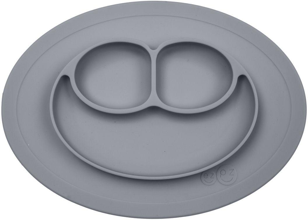 Ezpz Тарелка детская Mini Mat цвет серыйPCMMG005Ezpz Mini Mat - уменьшенная версия тарелочки-плейсмата Happy Mat. Предназначена для столиков для кормления и использования в поездках. Рекомендована для малышей от 4 месяцев. Тарелка тоньше, легче и компактнее, чем Happy Mat, но обладает теми же отличительными чертами: присасывается к столу, чтобы ребенок не смог ее перевернуть; подходит для микроволновки и посудомоечной машины; улыбается и вызывает у детей улыбку. Вмещает 240 мл. У тарелочки также есть удобный чехольчик с ручками, который легко можно взять с собой.Тарелка разработана и запатентована в США. Идея создания удобной безопасной посуды для детей принадлежит многодетной маме, которая как никто другой знает, как сложно уследить за детками во время еды и сохранить при этом чистоту и порядок. Благодаря такой тарелочке прием пищи становится веселым и безопасным, а кухня остается чистой и опрятной.