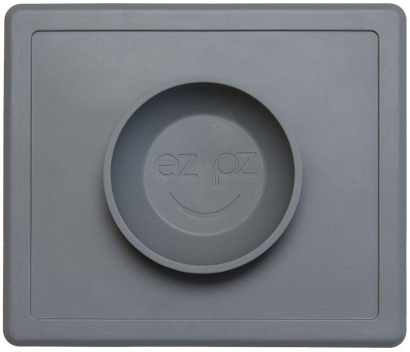 Ezpz Тарелка детская Happy Bowl цвет серый115510Ezpz Happy Bowl - силиконовая тарелка-плейсмат, которую невозможно перевернуть. Чаша высотой почти 4 см и объемом 240 мл идеально подходит для завтраков и обедов. Область плейсмата не дает ребенку испачкать стол. Тарелка изготовлена из силикона высочайшего качества и абсолютно безопасна. Не имеет липучек или присосок - фиксация происходит на любой ровной горизонтальной поверхности за счет плоской, гладкой поверхности тарелочки - мата. Подходит для использования в микроволновке и посудомоечной машине. Выглядит как улыбающаяся рожица, что очень нравится детям и их мамам. Тарелка разработана и запатентована в США. Идея создания удобной, безопасной посуды для детей принадлежит многодетной маме, которая как никто другой знает, как сложно уследить за детками во время еды и сохранить при этом чистоту и порядок. Благодаря такой тарелочке прием пищи становится веселым и безопасным, а кухня остается чистой и опрятной.