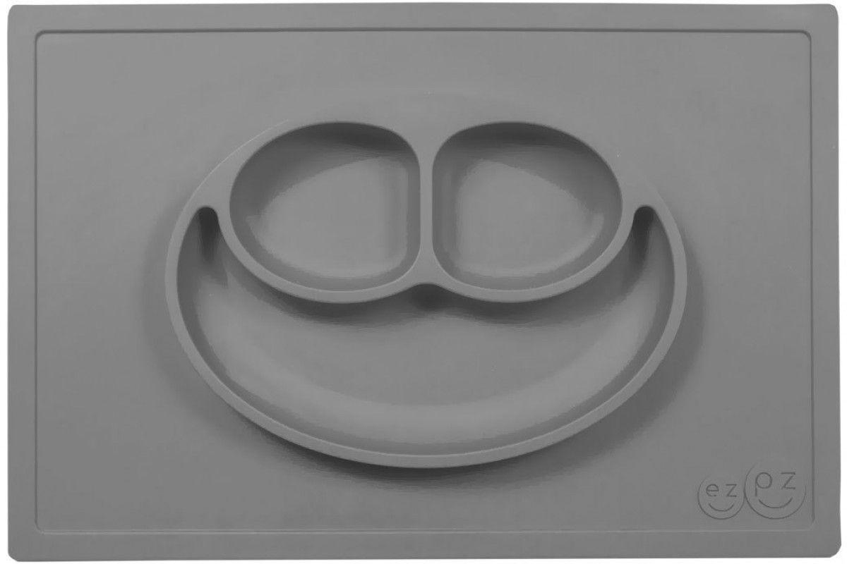Ezpz Тарелка детская Happy Mat цвет серыйPKHMA005Ezpz Happy Mat - необычная силиконовая тарелка-плейсмат, которая не имеет аналогов. Ее главная особенность заключается в том, что тарелку невозможно перевернуть или опрокинуть. С ней ребенок не сможет испачкать стол или, что гораздо важнее, обжечься горячей пищей.Изготовлена из силикона высочайшего качества и абсолютно безопасна. Не имеет липучек или присосок - фиксация происходит на любой ровной горизонтальной поверхности за счет плоской, гладкой поверхности тарелочки - мата. Подходит для использования в микроволновке и посудомоечной машине. Выглядит как улыбающаяся рожица, что очень нравится детям и их мамам.Тарелка разработана и запатентована в США. Идея создания удобной, безопасной посуды для детей, принадлежит многодетной маме, которая как никто другой знает, как сложно уследить за детками во время еды и сохранить при этом чистоту и порядок. Благодаря такой тарелочке прием пищи становится веселым и безопасным, а кухня остается чистой и опрятной.Объем 540 мл.