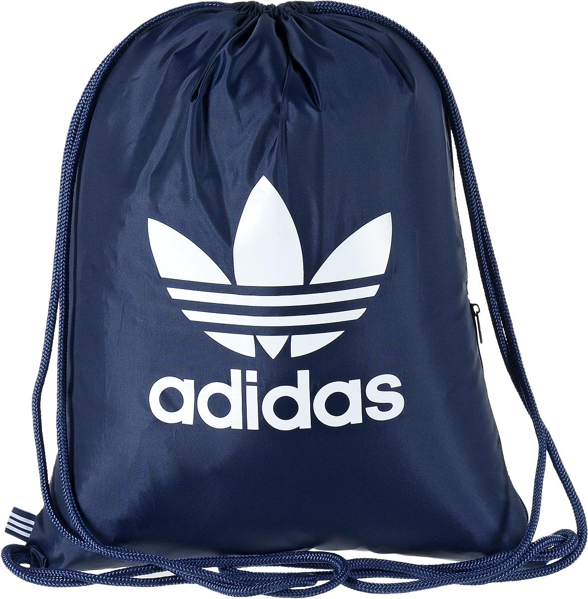 Рюкзак спортивный Adidas Trefoil, цвет: темно-синий, 23 л. BK6727RivaCase 7560 redСтильный спортивный рюкзак Adidas Trefoil выполнен из полиэстера и оформлен символикой бренда. Изделие имеет одно основное отделение, которое закрывается с помощью затягивающего шнурка. С внутренней стороны изделие оснащено удобной ручкой для переноски. Снаружи, с одной из боковых сторон находится прорезной карман на застежке-молнии. Веревочные завязки можно использовать как наплечные лямки. Стильный и функциональный рюкзак поместит все необходимое.