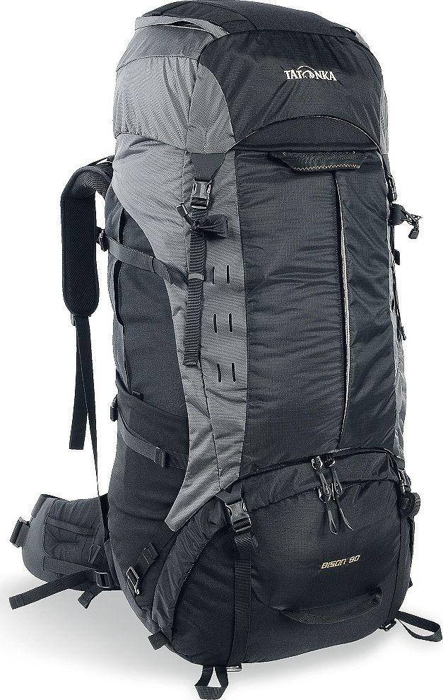 Рюкзак туристический Tatonka Bison, цвет: черный, 90+10 л67743Туристический рюкзак Tatonka Bison 90 - лучший выбор для тех, кто отправляется в длительный пеший поход c грузом, вес которого 25-35 килограмм. Благодаря системе подвески Х1, до 85% веса переносимого груза рюкзак перераспределит с плеч на бедра, тем самым спасая вашу спину и плечи от боли и усталости. Особенности рюкзака Tatonka Bison 90 Внешний вид В 2017 году Tatonka обновила дизайн и материалы рюкзака, благодаря чему он стал легче и современнее. Рюкзак выполнен из прочных материалов Cordura 500D, T-Square Rip и T-Snow Crust. Cordura с толщиной волокна 500 ден сочетает высокую прочность на разрыв и истирание классического волокна 1000 ден с легкостью материала 500 ден. Она делает рюкзак чрезвычайно прочным и износостойким. T-Square Rip и T-Snow Crust - лёгкие и прочные материалы, которые помогают снизить вес рюкзака. Система Х1 состоит из двух эргономично изогнутых X-образно скрещенных шин и полиэтиленовой пластины, необходимой для формирования профиля спины. Алюминиевые шины принимают основную нагрузку системы, перераспределяют ее на мощный набедренный ремень, состоящий из жесткой изогнутой 3D полиэтиленовой пластины и многослойной подушки, создающей комфортное прилегание ремня к бедрам. Посадка набедренного пояса удобно регулируется при помощи гибкой системы затяжки ремня. Материал ремня и анатомической спинной подушки максимально гладкий, чтобы не натирать бедра и спину. В нижней части ремня расположена вставка из Lumbar Pad для предотвращения соскальзывания рюкзака. За подушкой находится короткая алюминиевая шина анатомической формы, обеспечивающая оптимальную посадку рюкзака. Спинная прокладка над поясничной подушкой имеет вогнутую форму и прошитые секции для улучшения вентиляции, которые гарантируют плотное прилегание рюкзака к телу. При правильной регулировке поясной ремень ложится на верхнюю часть бедер и принимает 80-85% всей нагрузки. Остальные 15-20% нагрузки приходятся на плечевые ремни анат