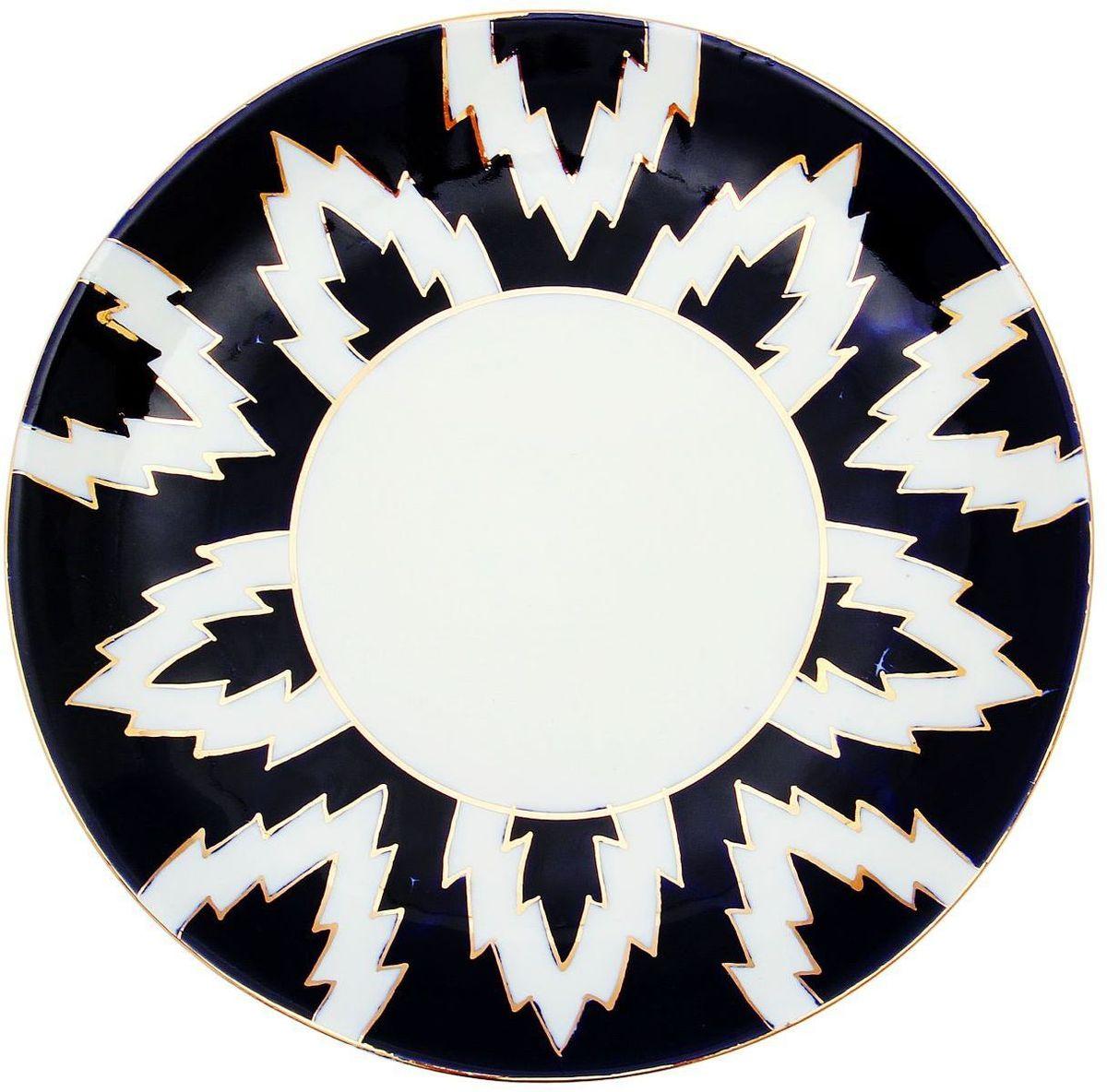 Тарелка Turon Porcelain Атлас, цвет: белый, синий, золотистый, диаметр 22,5 см1625406Узбекская посуда известна всему миру уже более тысячи лет. Ей любовались царские особы, на ней подавали еду для шейхов и знатных персон. Формулы красок и глазури передаются из поколения в поколение. По сей день качественные расписные изделия продолжают восхищать совершенством и завораживающей красотой.Данный предмет подойдёт для повседневной и праздничной сервировки. Дополните стол текстилем и салфетками в тон, чтобы получить элегантное убранство с яркими акцентами.Национальная узбекская роспись «Атлас» имеет симметричный геометрический рисунок. Узоры, похожие на листья, выводятся тонкой кистью, фон заливается тёмно-синим кобальтом. Синий краситель при обжиге слегка растекается и придаёт контуру изображений голубой оттенок. Густая глазурь наносится толстым слоем, благодаря чему рисунок мерцает.