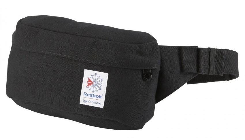 Сумка на пояс Reebok Cl Fo Waistbag, цвет: черный. BQ2233332515-2800Все, что тебе может понадобиться, должно всегда быть под рукой. И поэтому эта поясная сумка на молнии – то, что нужно. В нее легко поместятся телефон, ключи и бумажник. И, вуаля – твои руки свободны.Холщовая ткань для прочностиРазмеры: 25 х 14 х 7 см, объем: 3,3 лПередний карман на молнии для надежного хранения вещейПотайной карман на молнии с внутренней стороныПластиковая застежка и регулируемый поясной ремень для оптимальной посадкиОднотонная расцветкаВышитый классический логотип