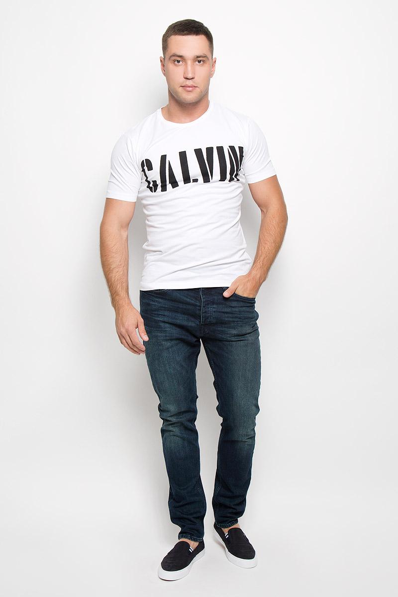 Футболка мужская Calvin Klein Jeans, цвет: молочный. J30J300139_1120. Размер XXL (54/56)R0216Т11Стильная мужская футболка Calvin Klein Jeans, выполненная из эластичного хлопка, обладает высокой теплопроводностью, воздухопроницаемостью и гигроскопичностью. Она необычайно мягкая и приятная на ощупь, не сковывает движения и превосходно пропускает воздух. Такая футболка отлично подойдет как для занятия спортом, так и для повседневной носки.Модель с короткими рукавами и круглым вырезом горловины - идеальный вариант для создания модного современного образа. Футболка оформлена крупным контрастным принтом с надписью Calvin. Эта модель подарит вам комфорт в течение всего дня и послужит замечательным дополнением к вашему гардеробу.