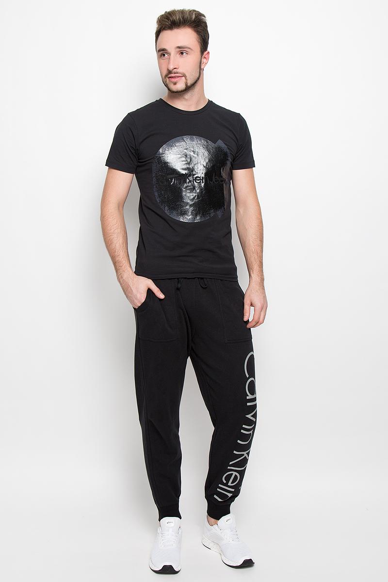 Футболка мужская Calvin Klein Jeans, цвет: черный. J30J301081. Размер XL (50/52)1588Стильная мужская футболка Calvin Klein Jeans, выполненная из натурального хлопка с добавлением эластана, обладает высокой теплопроводностью, воздухопроницаемостью и гигроскопичностью.Модель с короткими рукавами и круглым вырезом горловины - идеальный вариант для создания модного современного образа. Футболка оформлена крупным контрастным принтом с логотипом Calvin Klein.