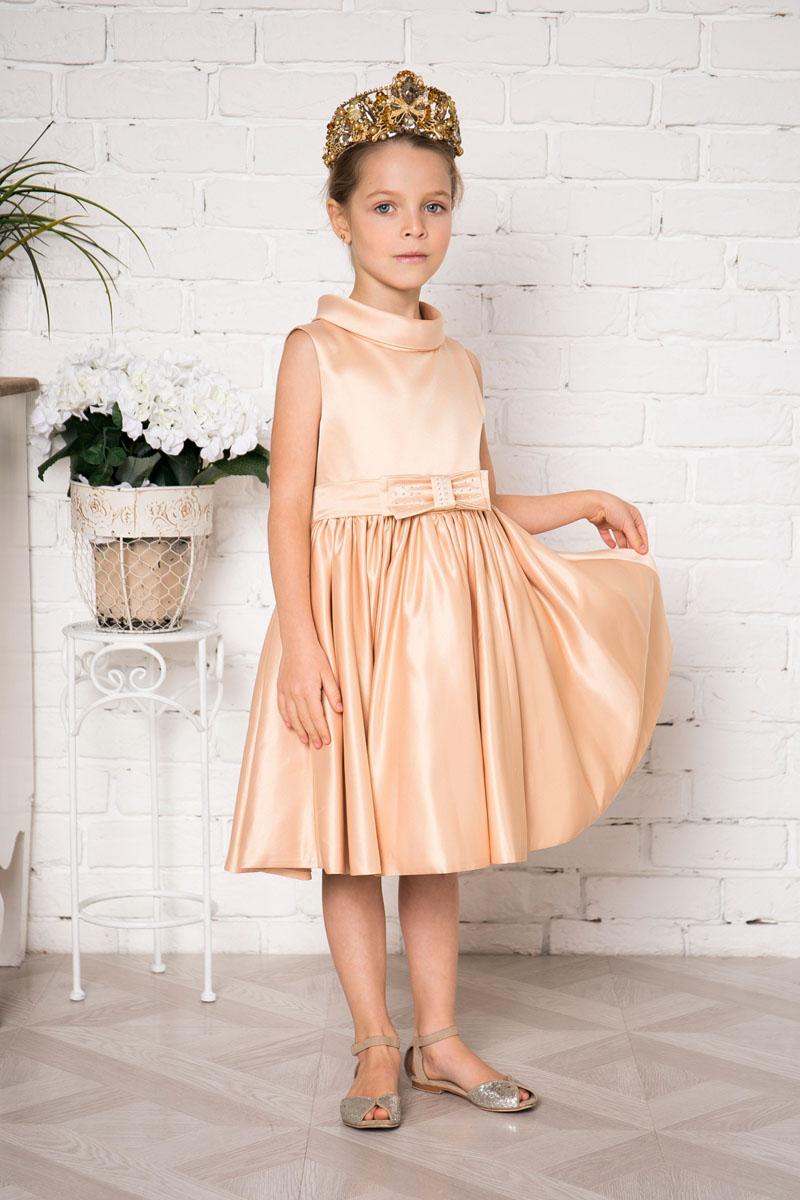 Платье для девочки Sweet Berry, цвет: бежево-золотой. 215907. Размер 128215907Платье для девочки Sweet Berry выполнено из высококачественного атласного материала и дополнено подкладкой из натурального хлопка. Модель сзади застегивается на потайную застежку-молнию. Сзади платье оформлено большим текстильным бантом, а также спереди небольшим бантом украшенным стразами.