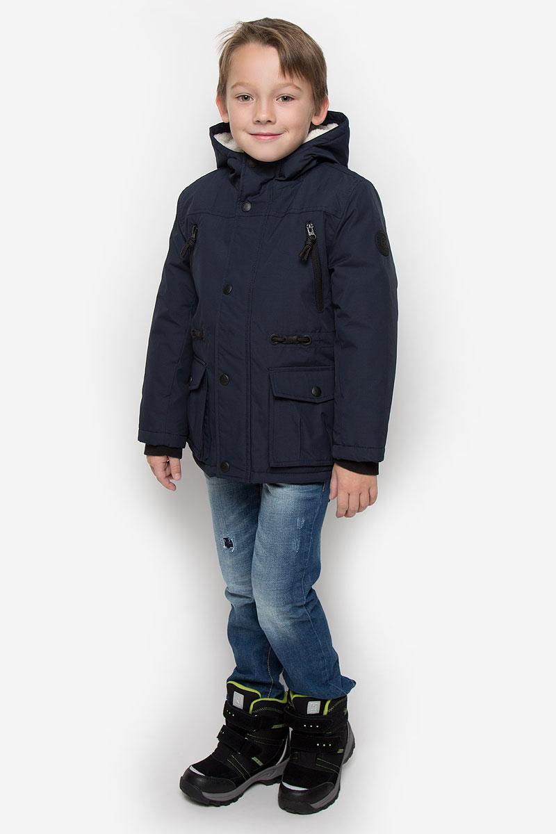 Куртка для мальчика Tom Tailor, цвет: темно-синий. 3533027.00.82_6800. Размер 116/1223533027.00.82_6800Куртка для мальчика Tom Tailor c длинными рукавами и несъемным капюшоном выполнена из прочного полиэстера. Подкладка капюшона выполнена из искусственного меха. Наполнитель - синтепон. Модель застегивается на застежку-молнию спереди и имеет ветрозащитный клапан на кнопках. Изделие имеет два втачных кармана на застежках-молниях и два накладных кармана с клапанами на кнопках спереди, а также внутренний накладной карман на липучке. Рукава оснащены внутренними флисовыми манжетами. Объем талии регулируется при помощи внутренней резинки с пуговицами.