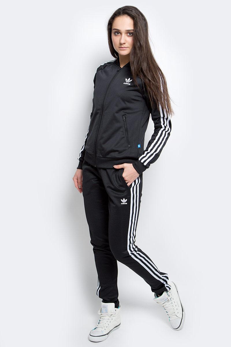 Толстовка женская adidas Supergirl Tt, цвет: черный. AJ8432. Размер 42 (48)AJ8432Культовая женская олимпийка - модель из блестящего трикотажа с аутентичными деталями в стиле adidas, такими как рифленый бейсбольный воротник, контрастные три полоски и прорезиненный Трилистник на спине. Рукава-реглан для максимально комфортной посадки. Карманы на лицевой стороне. Классический крой.
