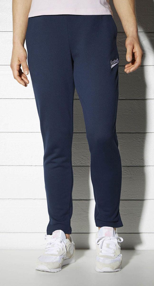 Брюки спортивные женские Reebok F Varsity Knit Pan, цвет: синий. BK2495. Размер S (42/44)BK2495Спортивные женские брюки Reebok F Varsity Knit Pan - классический стиль. Мягкая объемная ткань очень приятна на ощупь, а разрезы по бокам создают дополнительный комфорт. Элементы классического дизайна и обработка швов тесьмой придают образу законченности. Свободный крой совершенно не сковывает движения.Эластичный регулируемый пояс на шнурке.Прямой крой штанин с разрезами по бокам.Декоративная тесьма в полоску добавляет винтажные нотки.Удобные карманы по бокам.