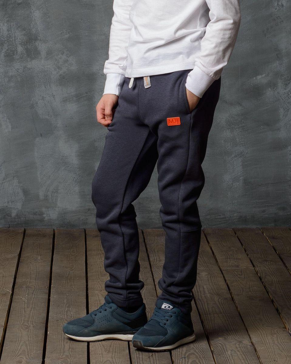 Брюки спортивные для мальчика Modniy Juk, цвет: серый. 15B00070702. Размер 110/11615B00070702/MJ_AUTHENTIC/Спортивные брюки Modniy Juk изготовлены из высококачественной мягкой ткани. Модель прямого кроя с комфортным мягкий поясом и манжетами из трикотажной резинки. Брюки дополнены боковыми карманами. Яркая нашивка в стиле Modniy Juk.