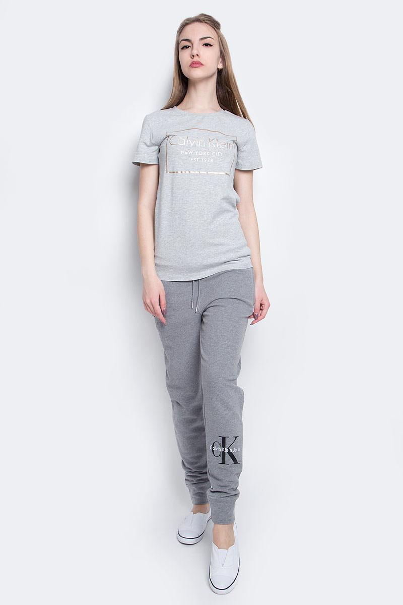 Футболка женская Calvin Klein Jeans, цвет: серый. J20J205315_0380. Размер XL (50/52)J20J205315_0380Женская футболка Calvin Klein Jeans изготовлена из высококачественного эластичного хлопка. Модель с короткими рукавами и круглым вырезом горловины украшена блестящим принтом с логотипом бренда.