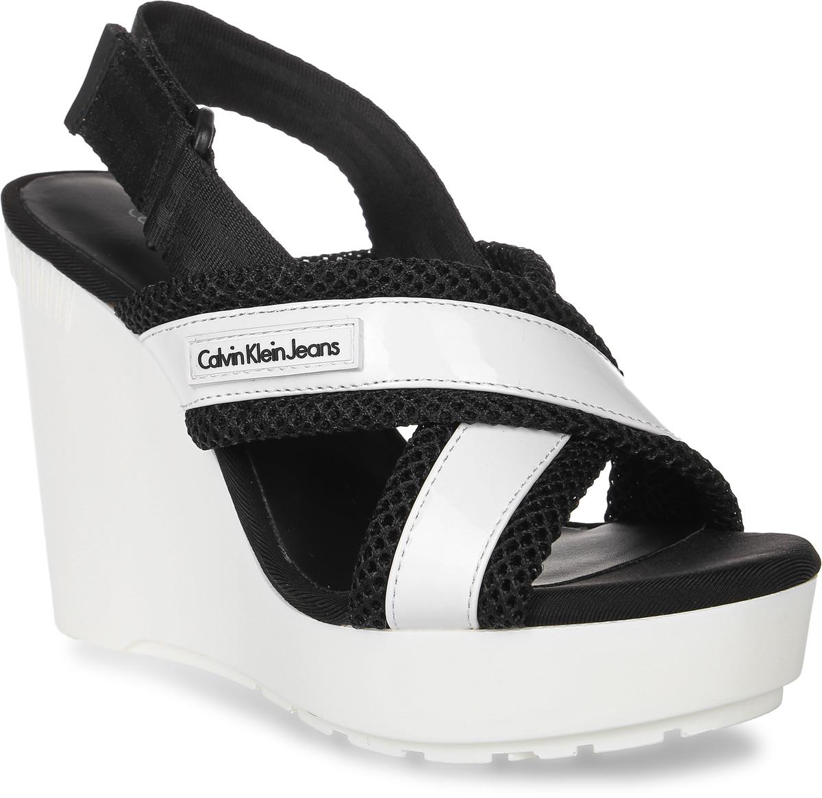 Босоножки женские Calvin Klein Jeans, цвет: черный, белый. R4972. Размер 38R4972Стильные босоножки от Calvin Klein Jeans - незаменимая вещь в гардеробе каждой женщины. Модель выполнена из текстиля и сетчатого материала в оригинальном дизайне. Перекрещивающиеся ремешки на подъеме прочно зафиксируют модель на вашей ноге, а застежка-липучка на щиколотке позволит отрегулировать объем. Высокая устойчивая танкетка выполнена из легкого ТЭП-материала. Подошва с рифлением обеспечивает отличное сцепление с поверхностью. Модные босоножки станут прекрасным завершением вашего летнего образа.