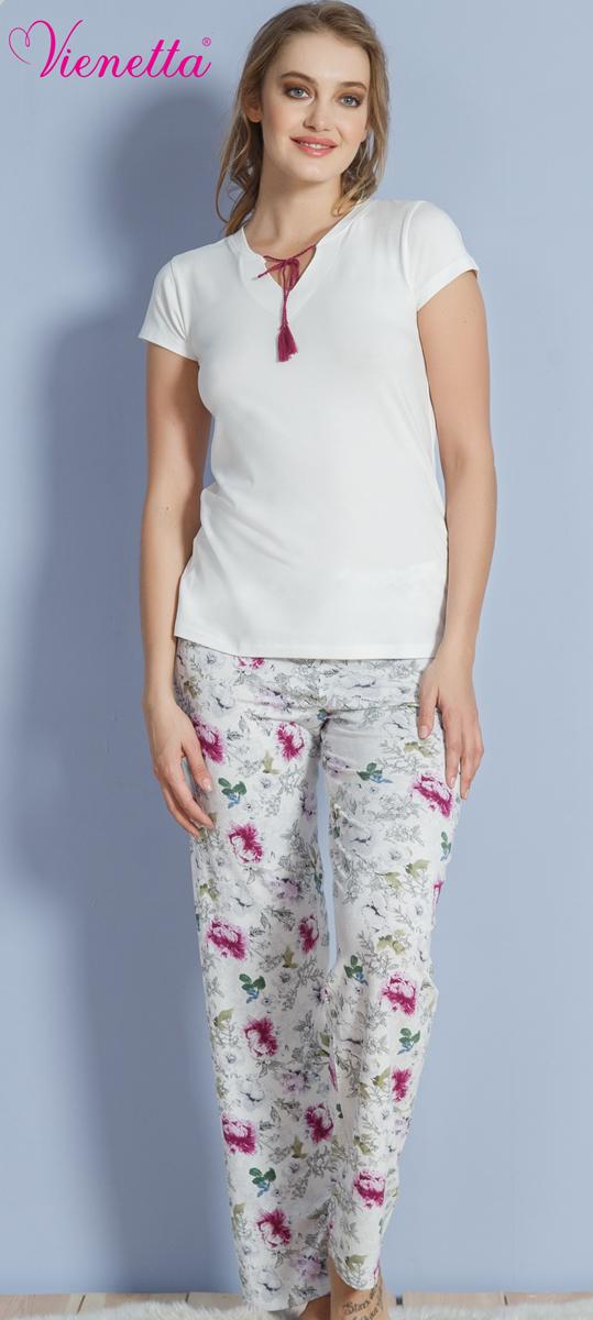 Комплект домашний женский Vienettas Secret: футболка, брюки, цвет: белый, розовый. 610348 1302. Размер M (46)610348 1302Женский домашний комплект Vienettas Secret состоит из футболки и брюк. Комплект выполнен из 100% натуральной вискозы. Футболка имеет V-образный вырез горловины, декорированный шнурком, и короткие рукава. Брюки свободного кроя снабжены резинкой на талии. Футболка выполнена в однотонном дизайне, а брюки дополнены цветочным принтом.