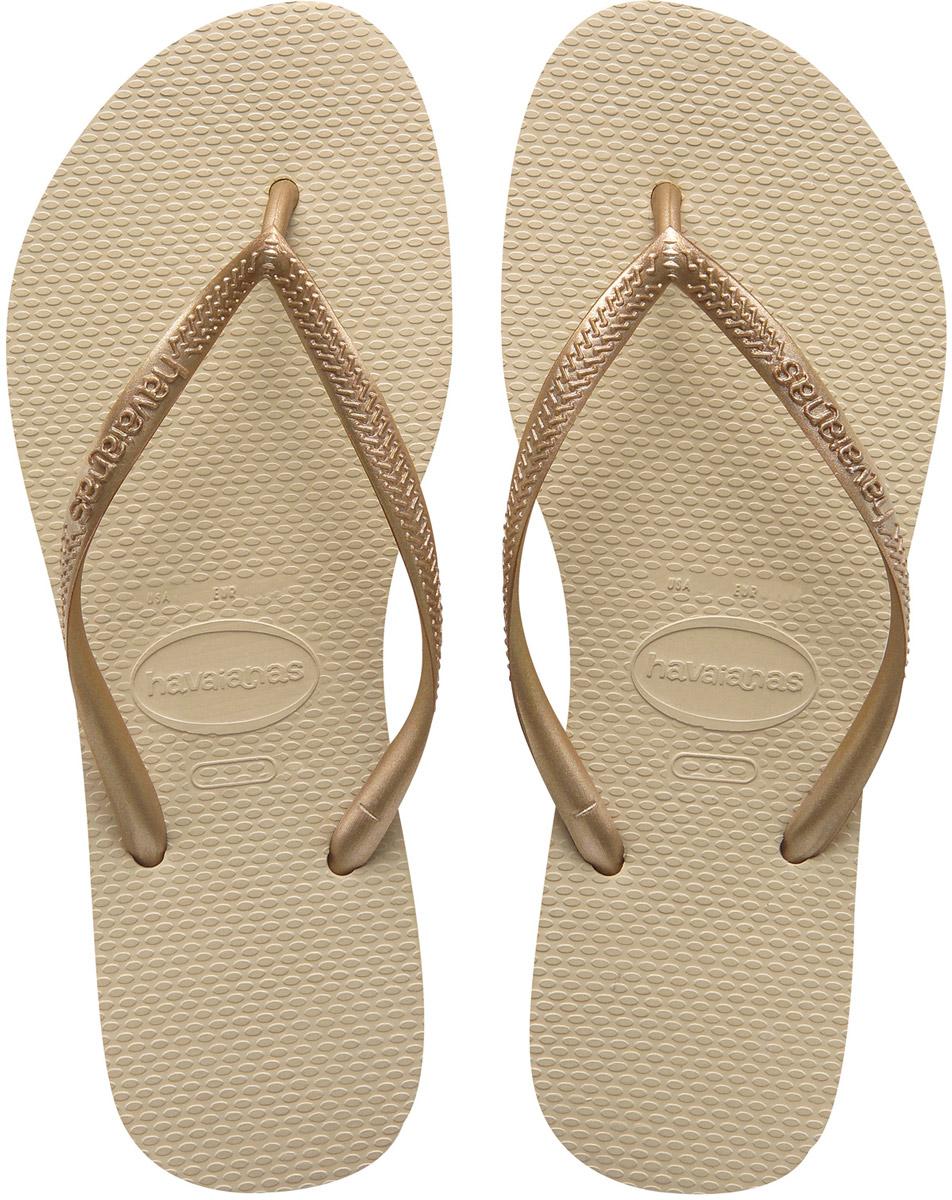 Сланцы женские Havaianas Slim, цвет: бежевый. 40000302719. Размер 39/40 (40/41)4000030-2719Модные сланцы Slim от Havaianas придутся вам по душе. Верх модели, выполненный из резины, оформлен рельефным орнаментом и названием бренда. Ремешки с перемычкой гарантируют надежную фиксацию модели на ноге. Подошва выполнена из материала ЭВА. Рифление на верхней поверхности подошвы предотвращает выскальзывание ноги. Рельефное основание подошвы обеспечивает уверенное сцепление с любой поверхностью. Удобные сланцы прекрасно подойдут для похода в бассейн или на пляж.