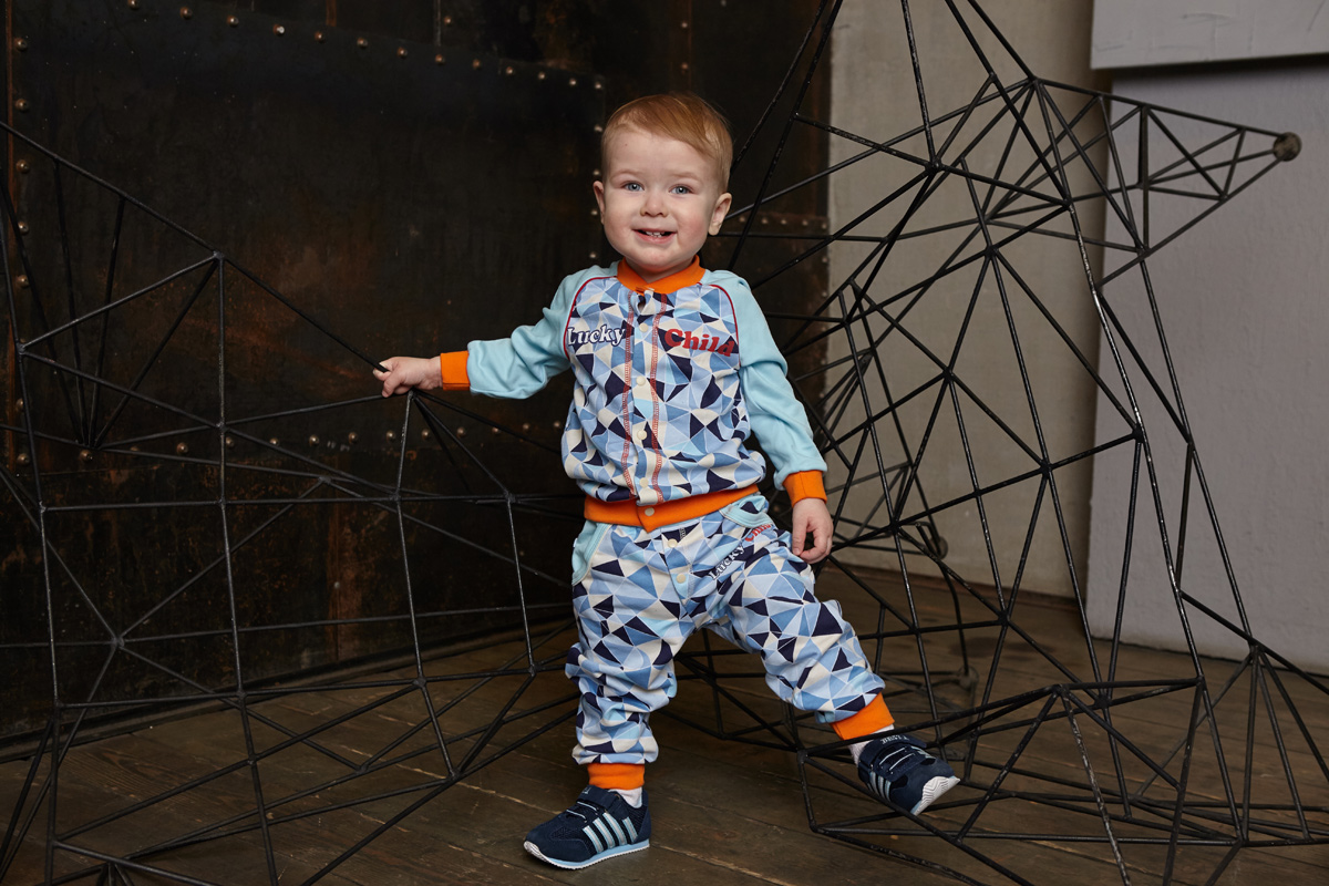 Кофта для мальчика Lucky Child, цвет: голубой, синий. 32-20. Размер 74/8032-20Сочетание холодного голубого цвета и бело-синего принта «треугольники» напоминает о далёких северных морях и ледоколах. Нашивка на рукаве делает вещь похожей на клубную куртку.