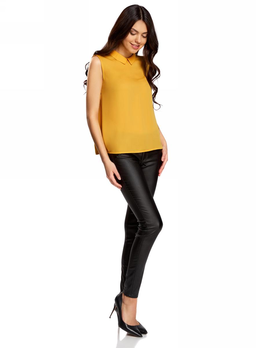 Блузка женская oodji Ultra, цвет: желтый. 11411084B/43414/5200N. Размер 40-170 (46-170)11411084B/43414/5200NЛегкая блузка прямого кроя без рукавов с воротником под горло. Особенности этой модели - глубокий вырез-капля с застежкой на крючки на спинке и небольшой округлый отложной воротничок. Блузка прямого силуэта из эластичной ткани отлично сидит и не стесняет движений. Маленькая блузка, по сути топ, - настоящая находка для любителей минимализма в одежде. С ней можно создать множество интересных образов - от строгих деловых до повседневных в стиле casual. Базовая блузка без рукавов отлично сочетается с прямыми брюками и юбкой-карандашом. Она скромная и в то же время элегантная. В комплекте с броскими аксессуарами эта модель прекрасно подойдет для нарядных выходов. Блузку можно носить навыпуск или заправленной внутрь. Она хорошо смотрится с джинсами, шортами и короткими юбками. Если хотите создать романтический образ, попробуйте сочетать блузку без рукавов с длинной или пышной юбкой, добавив клатч или сумочку. С этой универсальной блузкой вы сможете создать оригинальные и неповторимые образы, которые подчеркнут ваш стиль.