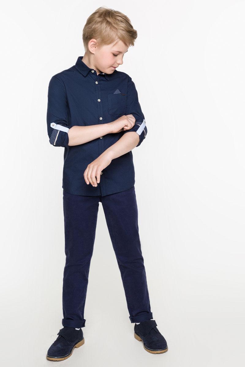 Рубашка для мальчика Acoola Ares, цвет: темно-синий. 20100280014_600. Размер 15820100280014_600Рубашка для мальчика Acoola Ares изготовлена из натурального хлопка. Модель с отложным воротником и длинными рукавами застегивается на пуговицы. Длину рукавов можно изменить с помощью хлястиков с пуговицами. На груди расположен накладной карман, декорированный металлической пластиной.
