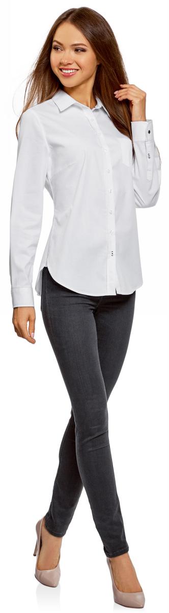 Рубашка женская oodji Ultra, цвет: белый, темно-синий. 11403205-11/18193/1079B. Размер 36-170 (42-170)11403205-11/18193/1079BБазовая классическая рубашка с отложным воротником. Модель слегка приталенного силуэта, который формируется за счет вытачек на спине. На груди небольшой накладной карман. Застежка и манжеты на пуговицах, низ рубашки закруглен. Хлопковая ткань с добавлением эластана легкая и приятная на ощупь, дышит и не раздражает кожу, легко стирается и сохнет. Приталенная рубашка отлично смотрится на самых разных фигурах. Базовая рубашка приталенного кроя подойдет для создания сдержанных и лаконичных деловых образов. Она хорошо сочетается с классическими брюками со стрелками, с прямыми юбками. Для создания более неформальных образов рубашку можно надеть с джинсами. Сверху комплект легко дополнить жакетом или кардиганом. Рубашку с закругленным низом можно носить заправленной или навыпуск. Выбор обуви зависит от стиля созданного вами образа. Это могут быть туфли на каблуке или лоферы, ботинки на плоской подошве, сапоги или ботильоны. В этой удобной рубашке вам будет комфортно в любой обстановке.