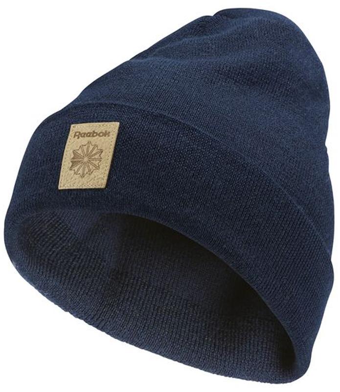 Шапка Reebok Cl Fo Beanie, цвет: синий. CD1376. Размер 58/60CD1376Эта шапка классического дизайна ? своего рода дань уважения богатому спортивному наследию. Классическая модель с отворотом всегда выглядит актуально и надежно защищает от холода. А кожаная нашивка с логотипом придает образу стильную нотку.Материал: 70% полиакрил / 30% шерсть, свитерная вязкаСвободная посадкаДвухслойный дизайн для дополнительного тепла и стильного образаРегулируемый отворотТисненый кожаный логотип