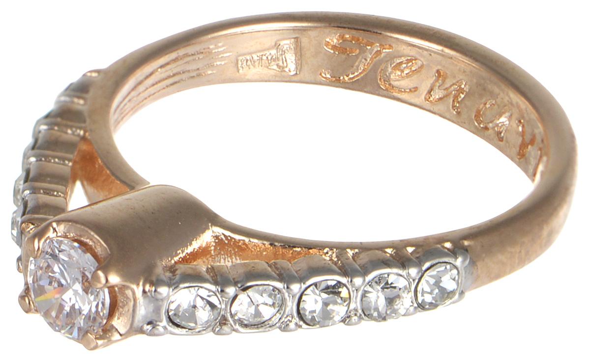 Кольцо Jenavi Teona. Энами, цвет: золотой. f428q0a0. Размер 17Коктейльное кольцоКольцо Jenavi Энами из коллекции Teona изготовлено из гипоаллергенного ювелирного сплава с позолотой и украшено чарующими фианитами. Дизайн этого кольца можно назвать элегантным и утонченным: классическая форма украшения будет хорошо смотреться на любой руке, а ряд сверкающих кристаллов по периметру аксессуара радует бесконечной красотой своих бликов. Изделие декорировано тиснением с названием коллекции изнутри. Если Вы находитесь в поиске аксессуара, который будет хорошо смотреться и в будние, и в праздничные дни, это кольцо - именно то, что Вам нужно! Классическая форма украшения легко впишется в офисный дресс-код, а блеск прозрачных фианитов будет уместен в любом праздничном образе