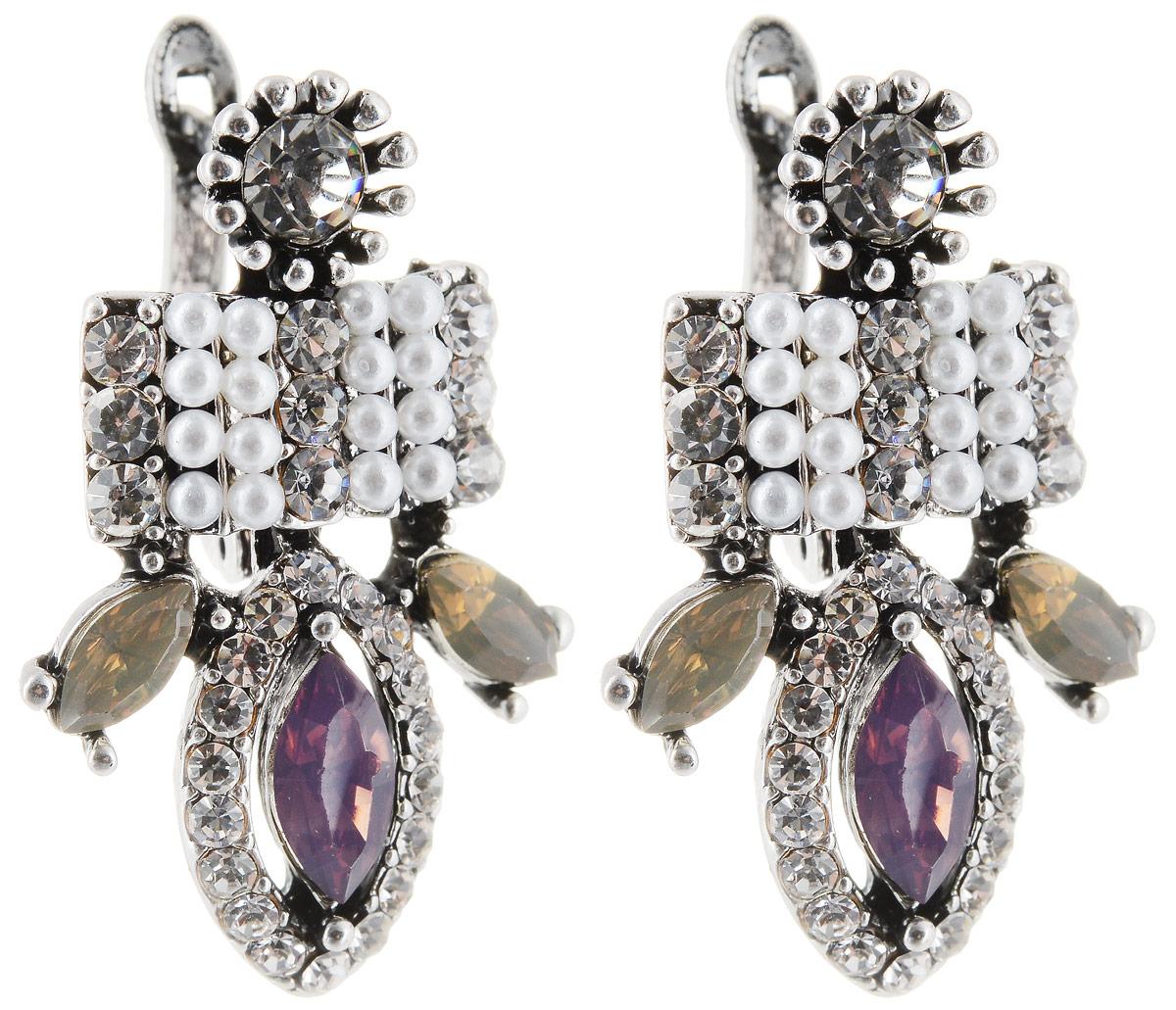 Серьги Taya, цвет: серебристый, пурпурный. T-B-12954Серьги с подвескамиСерьги с английским замком. Некрупные, с мелкими деталями оформлены вставками из пастельных кристаллов. Много страз: есть блестящие, есть матовые белые. Металл в глубине слегка тонированный.